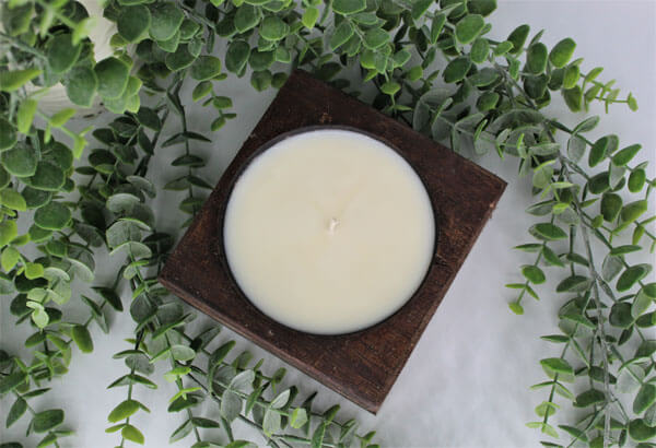 A top-down view of a candle in a square wooden vessel, against a blank background and surrounded by eucalyptus.