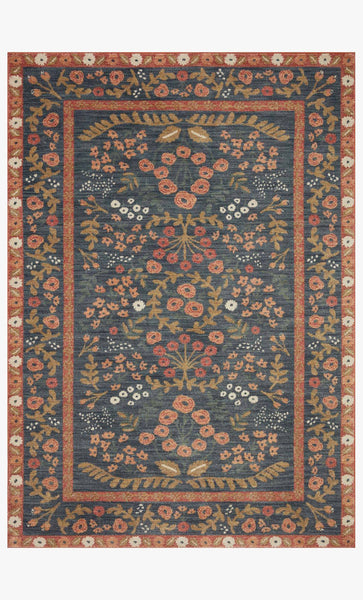A rectangular rug with a navy background and rust-colored borders on the edge and part-way in. It has a symmetrical floral pattern.
