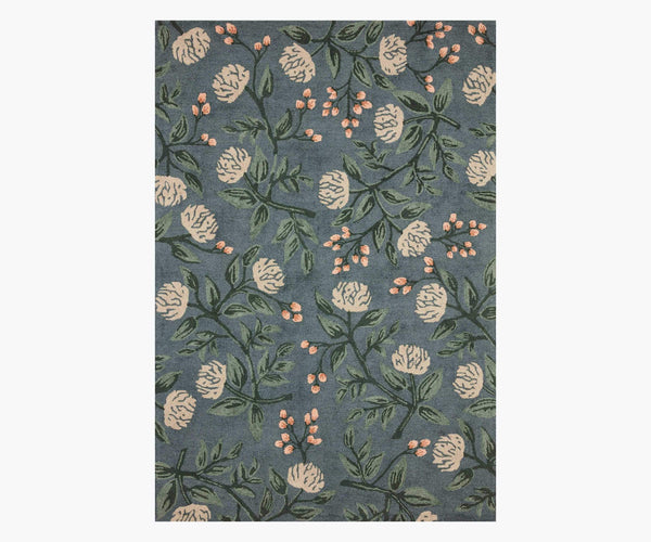 A rectangle rug with a dusty blue background. The rug is patterned with stems of peony flowers and buds.