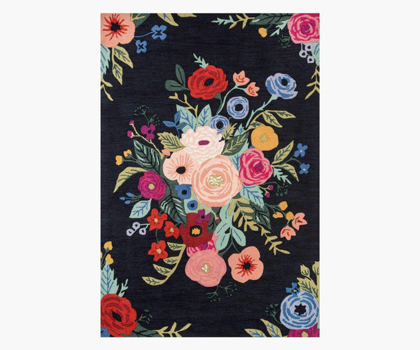 A rectangular rug with a black background. It has a loose border of red, pink, and blue flowers and features a multicolored bouquet of florals and leaves in the center.