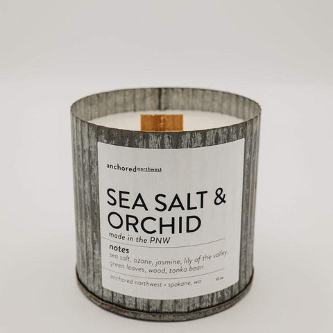 A candle in a galvanized metal tin with a wood wick sits on a blank background. The label reads Sea Salt & Orchid.
