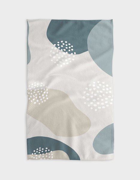 A rectangular tea towel with organic blob shapes on an off-white background. The shapes are cream and shades of teal. There are sections with circles of small white dots over the shapes.