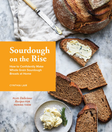 """A book cover with an orange square in the left side of the middle of the page, with white text that says """"Sourdough on the Rise"""". A loaf of brown bread is cut into slices and scattered on a marble background."""