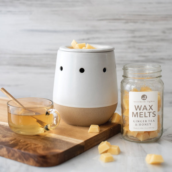 """A ceramic wax melter is on a wooden board. It is next to a jar of wax melts labeled """"Ginger Tea & Honey"""". There is a mug of tea and several cubes of wax melts scattered around."""