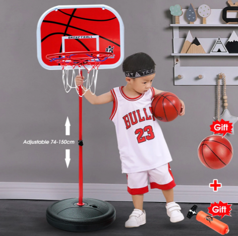 Little boy in basketball uniform, Bulls 23, with headband grasping basketball in one hand and pole in the other, looking astounded at two Gifts: basketball & air pump