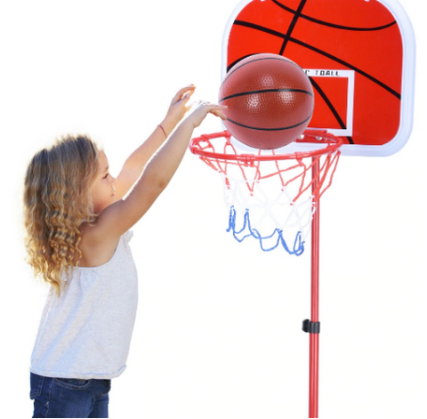 Young girl pitching basketball into net