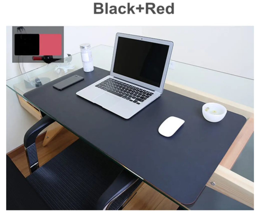 Mouse pad pink on work desk with black/red reversible colors displayed on easel