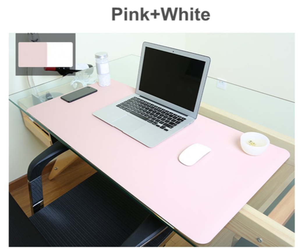 Mouse pad pink on work desk with pink/white reversible colors displayed on easel