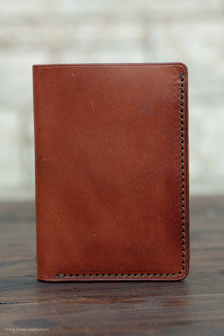 A tall minimalist leather wallet shown in buck brown with olive stitching standing on a wooden table with a white background.  It is closed with the front face showing.