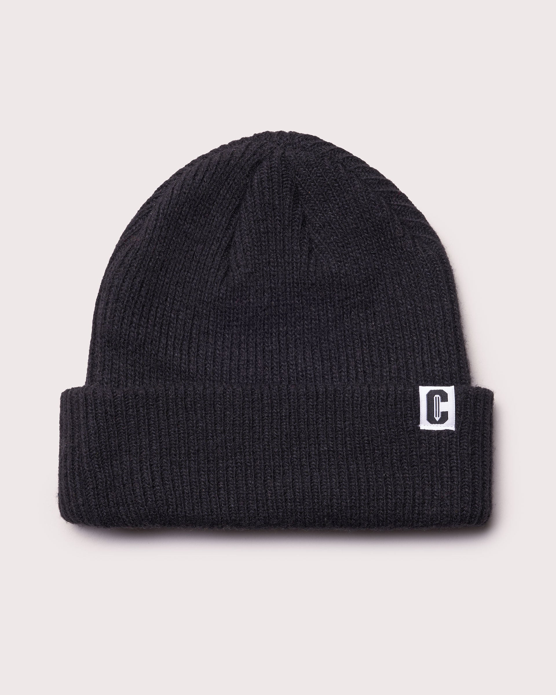 A black merino wool cuffed beanie with a woven label featuring the Coursework C logo.