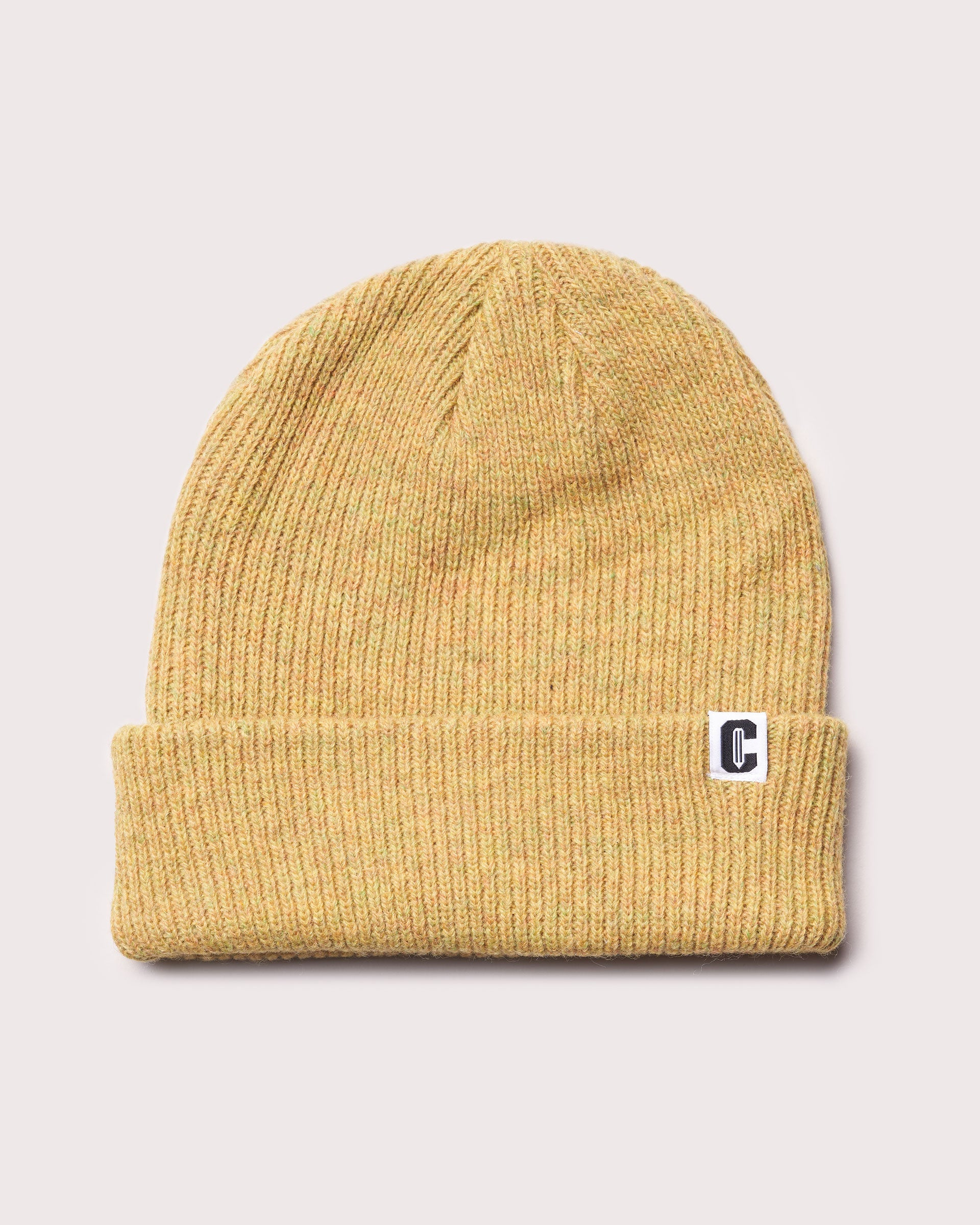 A mustard yellow merino wool cuffed beanie with a woven label featuring the Coursework C logo.