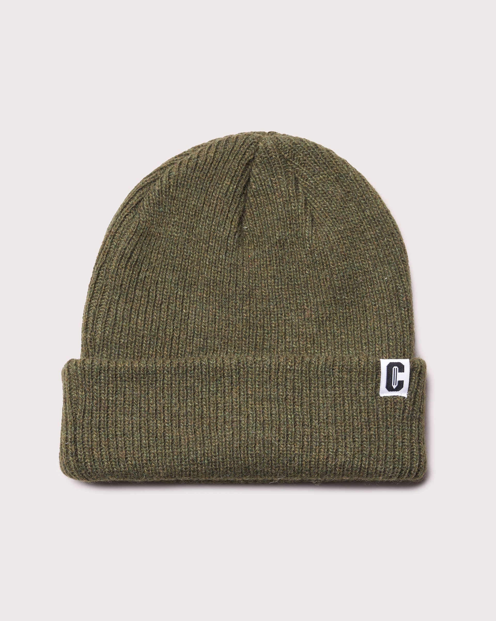 An olive green merino wool cuffed beanie with a woven label featuring the Coursework C logo.