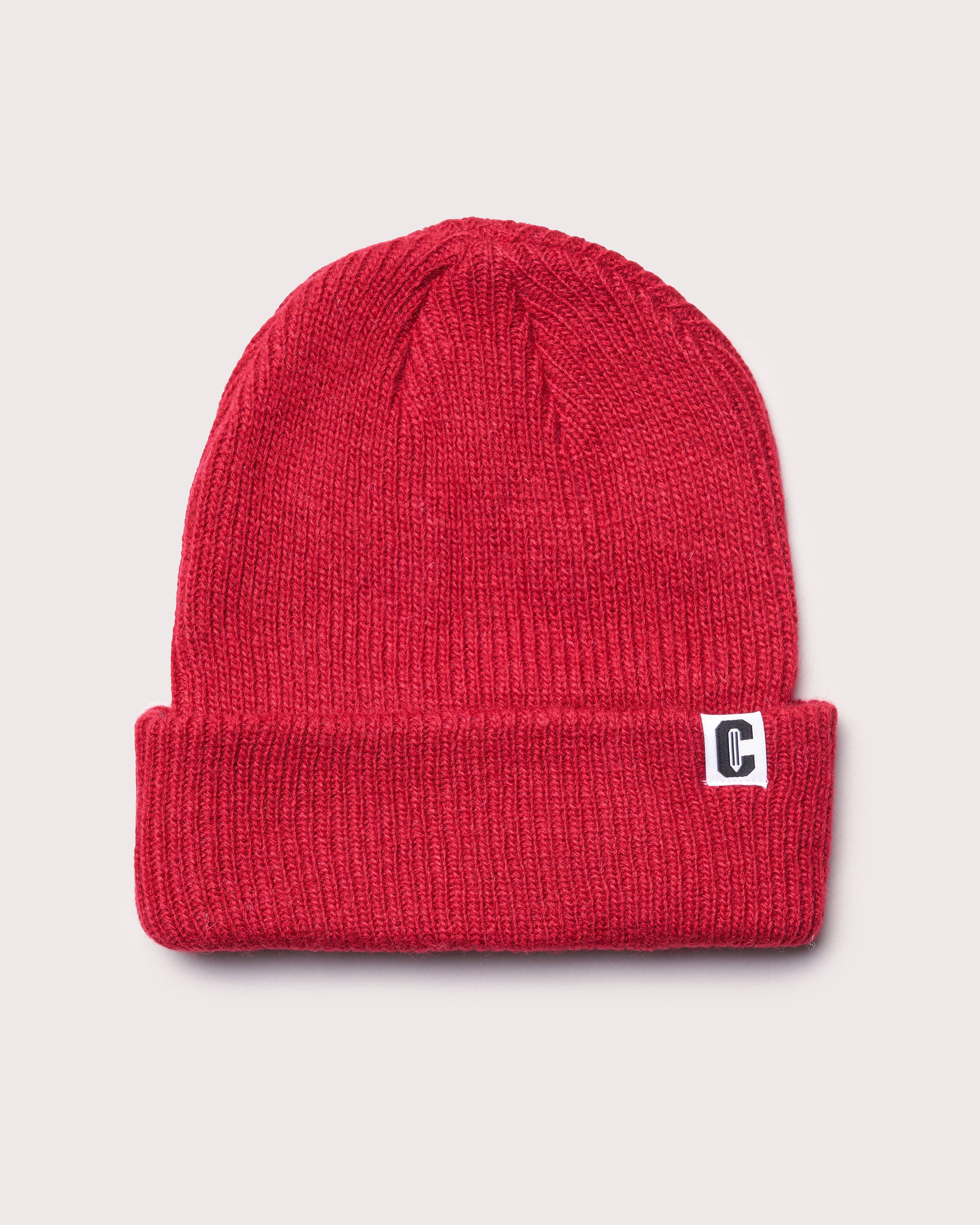A red merino wool cuffed beanie with a woven label featuring the Coursework C logo.