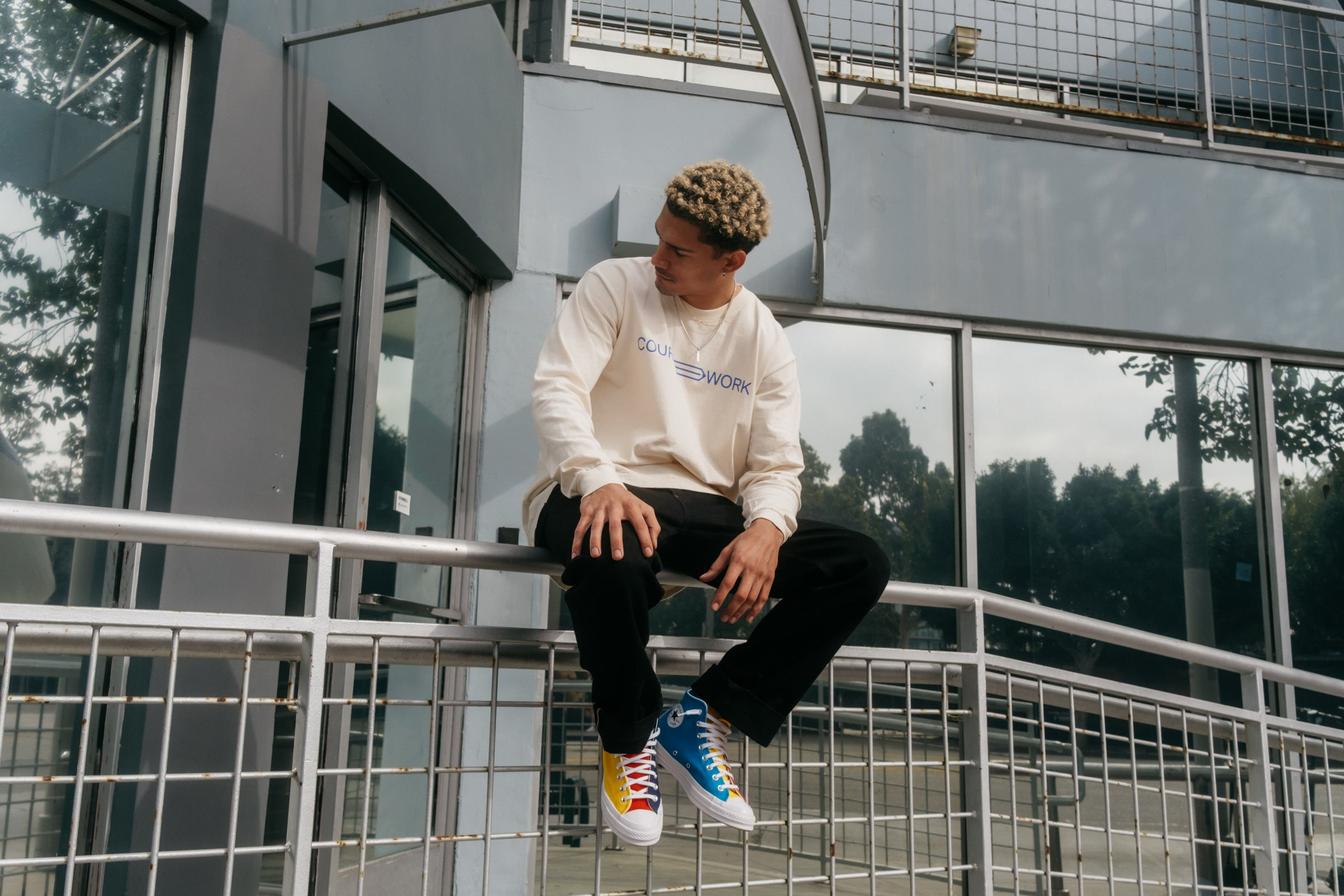 Model wearing the Full Width Text Long Sleeve Tee and sitting on a handrail.