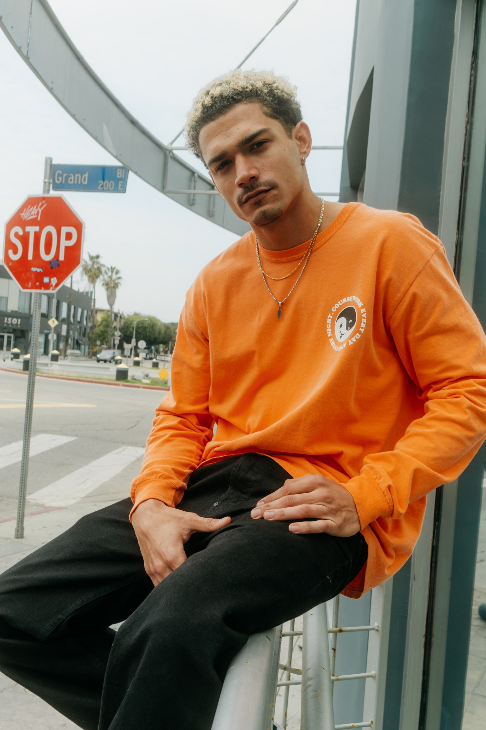 Model wearing the Day and Night Long Sleeve Tee in orange and sitting on a handrail.