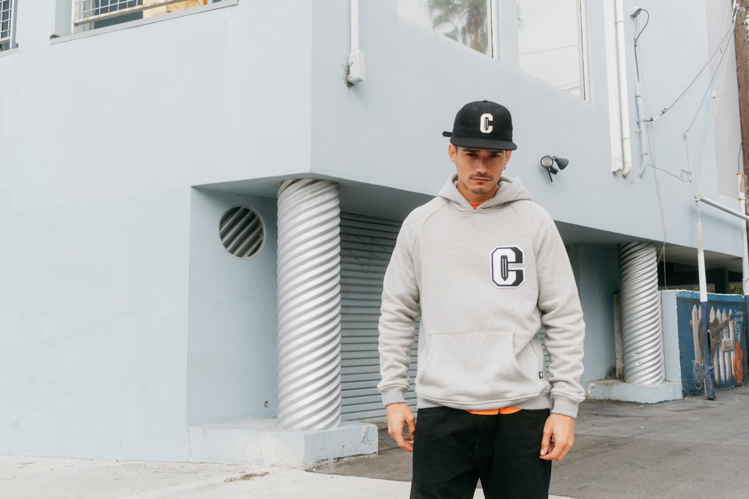 Model wearing the Varsity C Hoodie in grey and the Ebbets Wool C Cap in black and standing in front of a building.
