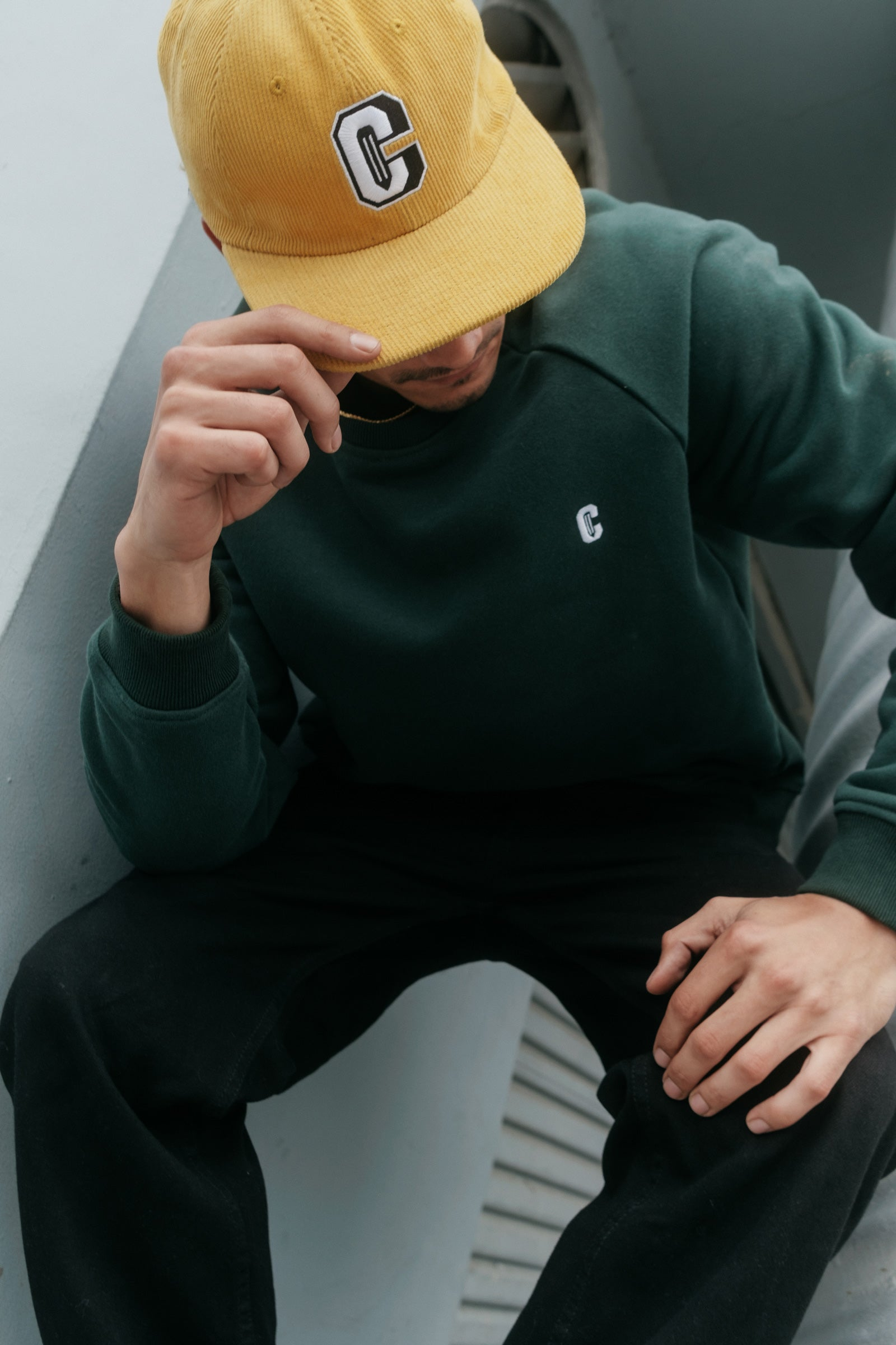 Model wearing the Varsity C Corduroy Cap in yellow and Icon Crewneck Sweatshirt in forest green and sitting at the corner of a building.
