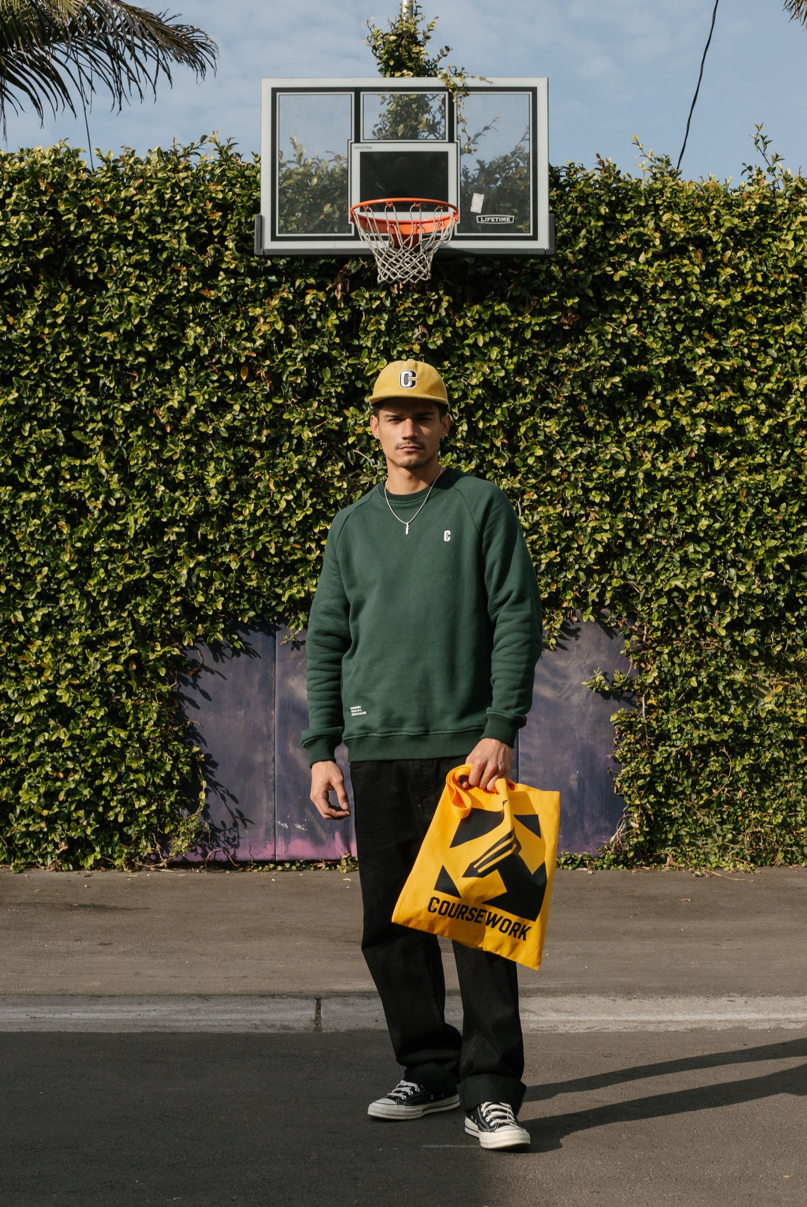 Model wearing the Varsity C Corduroy Cap in yellow and Icon Crewneck Sweatshirt in forest green and standing in front a basketball hoop and foliage..