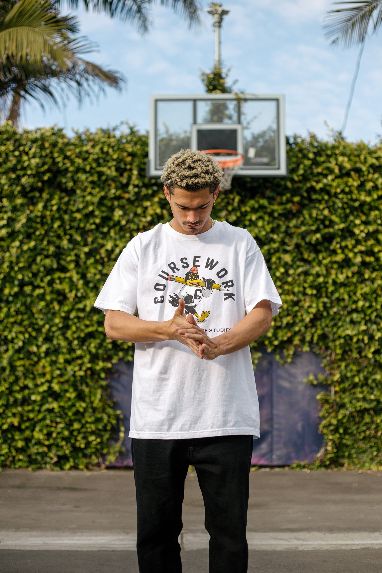 Model wearing the Early Birds tee with a basketball hoop and green foliage behind him.