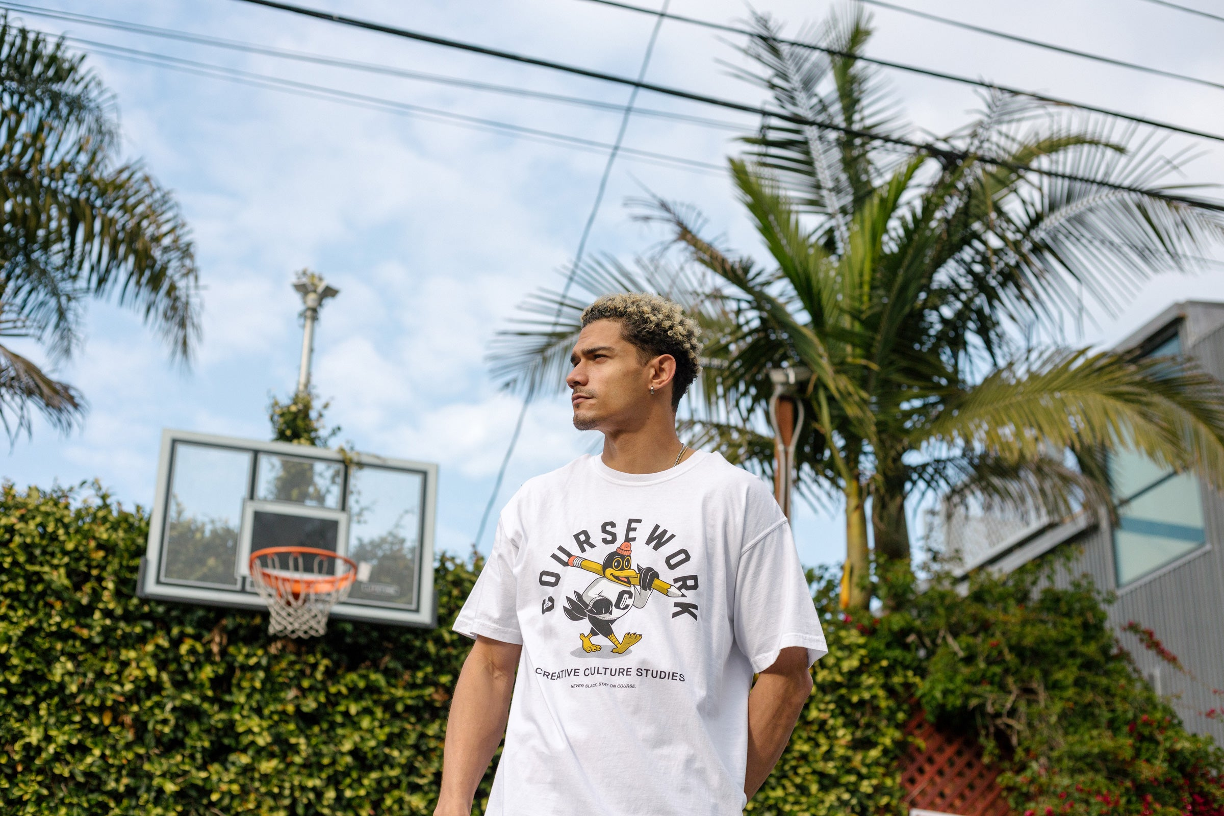 Model wearing the Early Birds tee with a basketball hoop, palm tree and green foliage behind him.