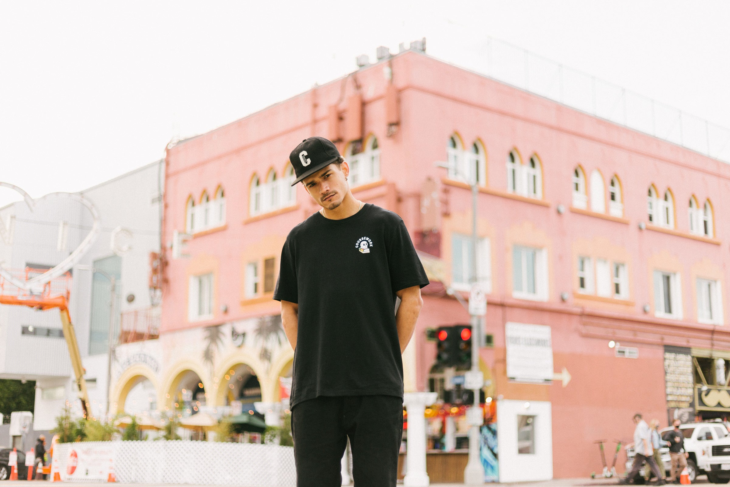 Model wearing the Ebbets Wool C Cap in black and the Required Reading Tee in black while standing on the sidewalk of an intersection.