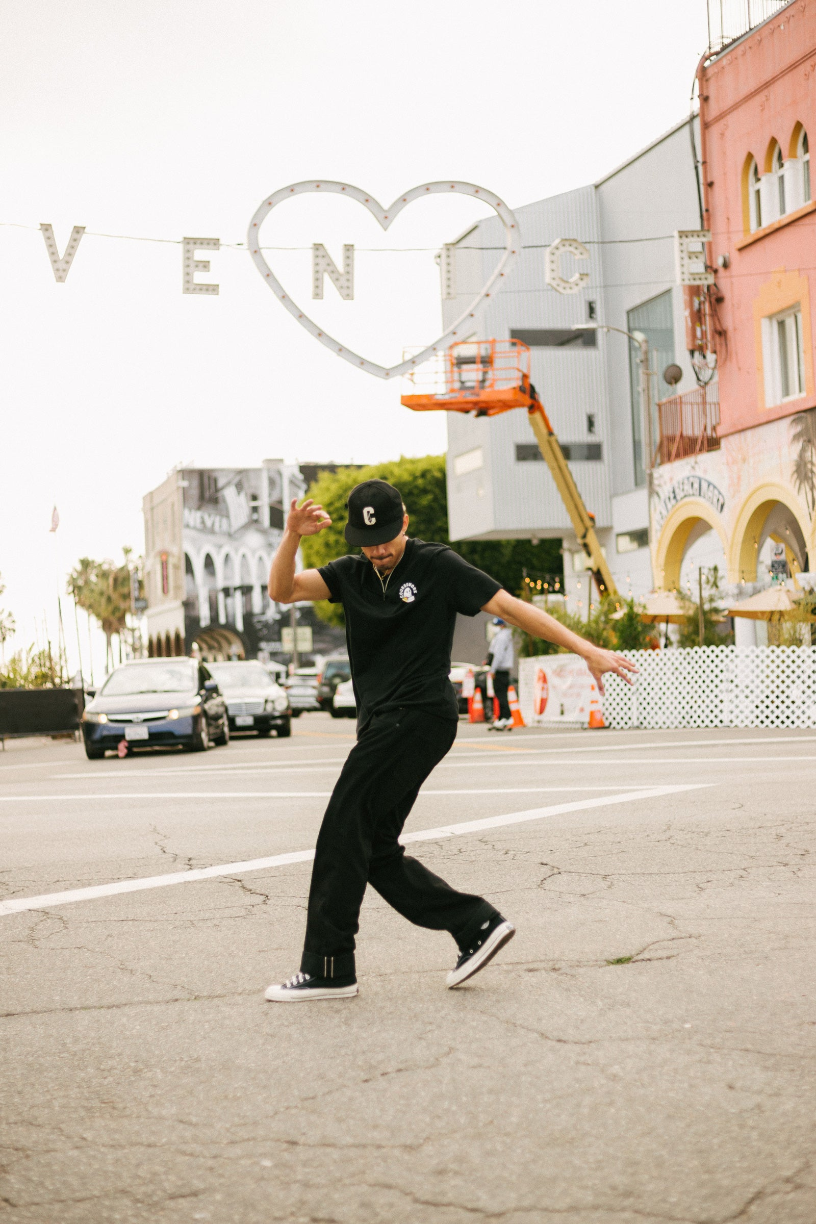 Model wearing the Ebbets Wool C Cap in black and the Required Reading Tee in black while breakdancing in the street.