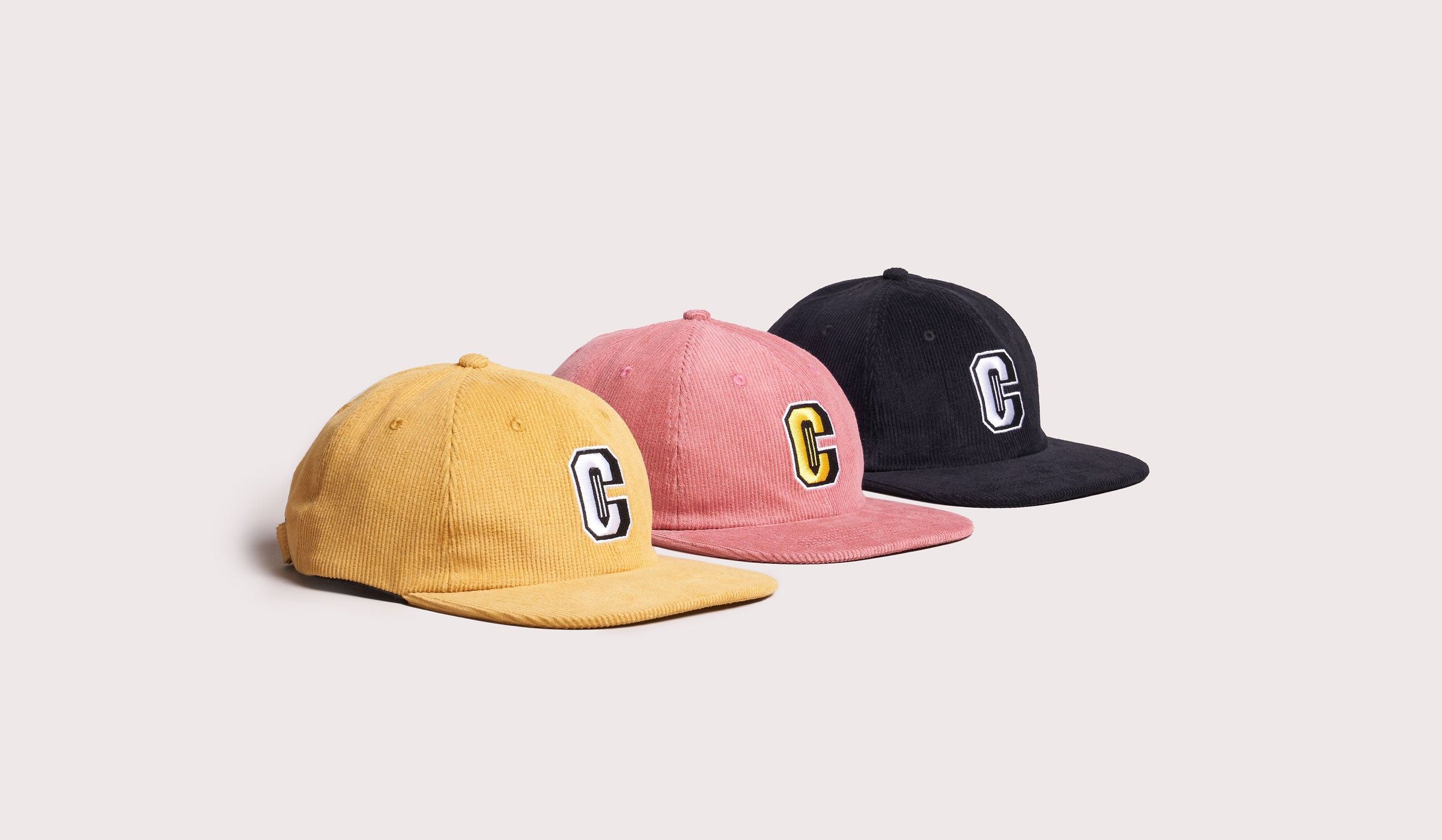 A group of three caps lined up from a side view.