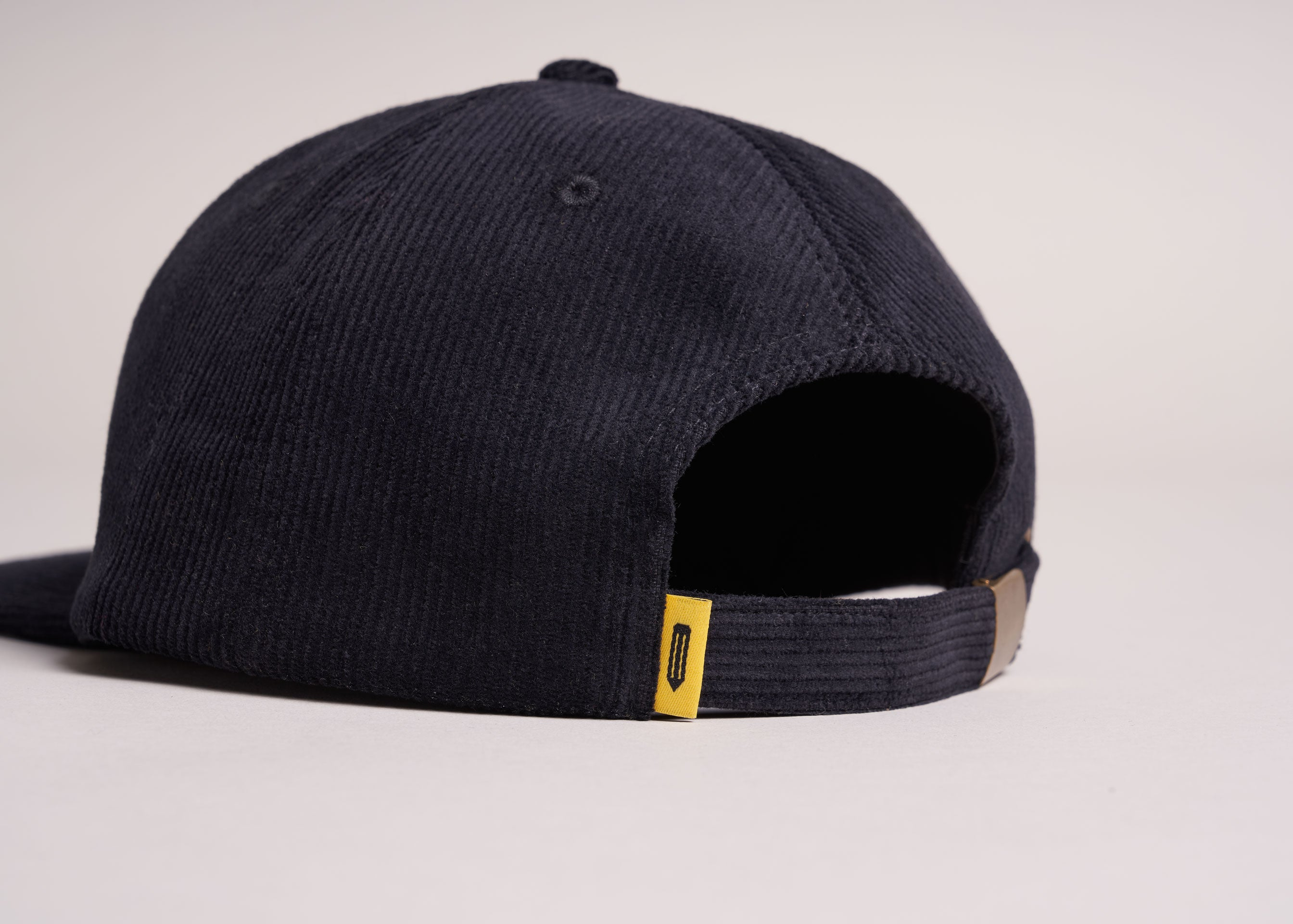 A backside view of a black unstructured corduroy cap with a yellow tag.