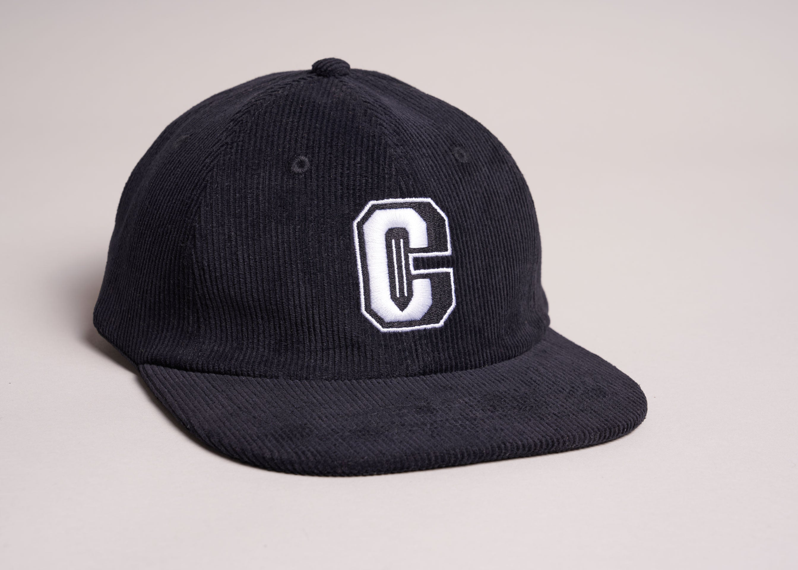A black unstructured corduroy cap with an embroidered varsity style C Coursework logo.