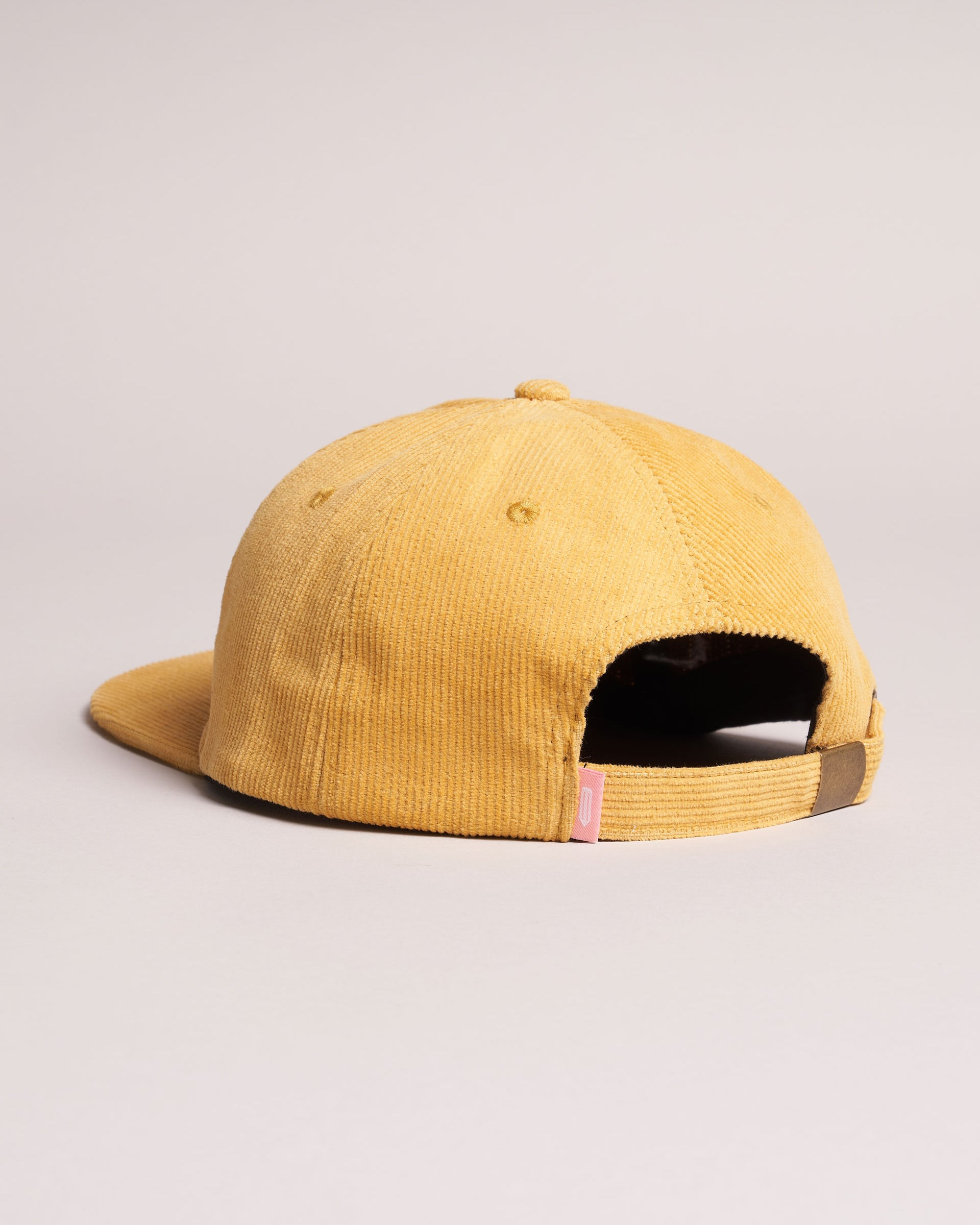 A backside view of an unstructured corduroy cap with a pink tag.