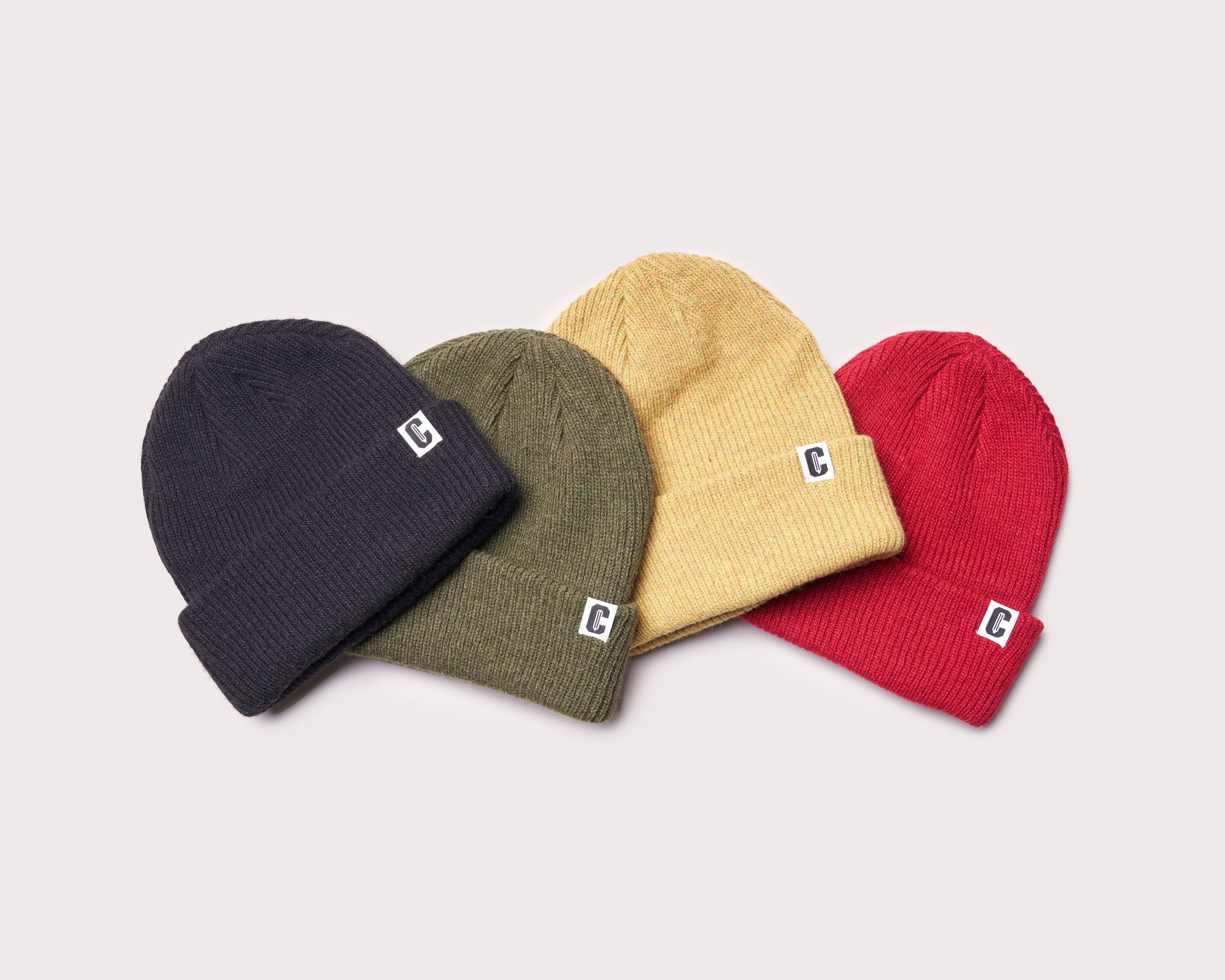 Four beanies arranged in a staggered layout