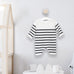 breton baby onesie hanging in room