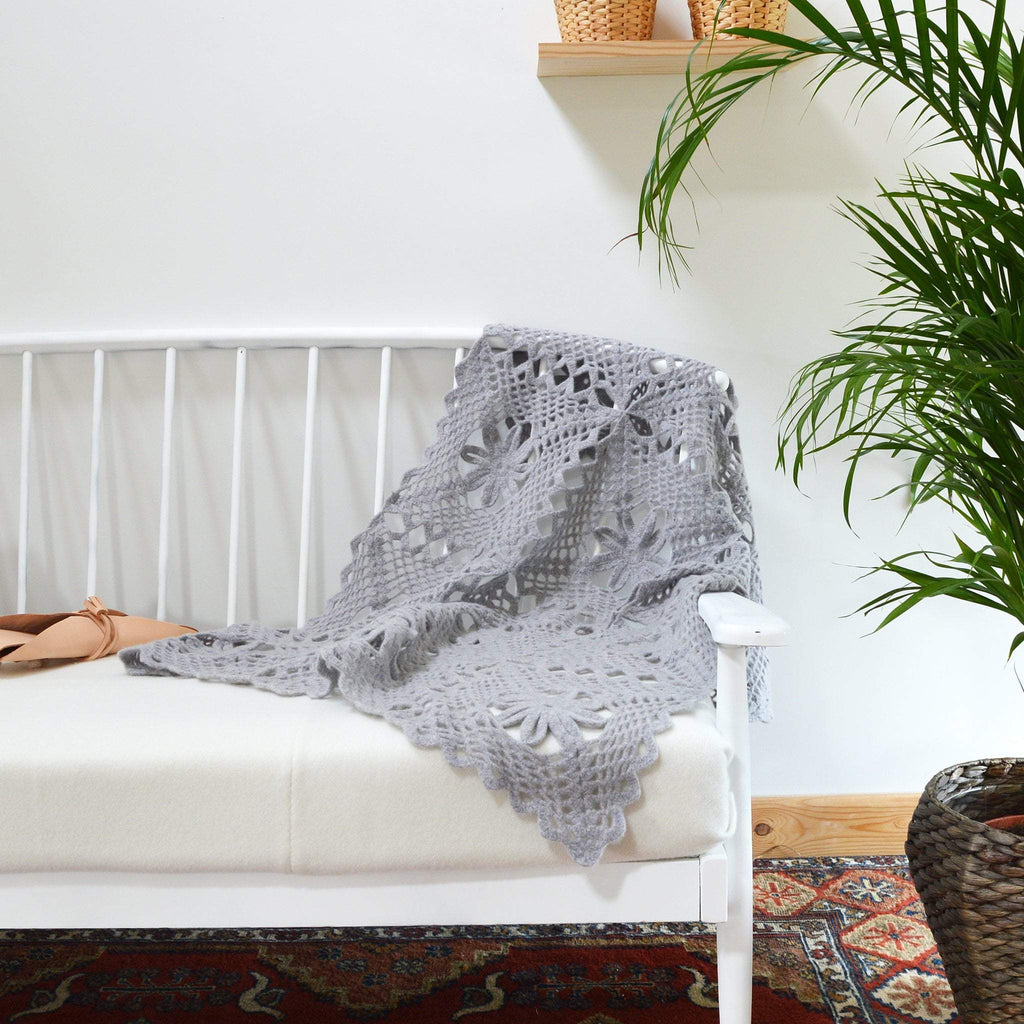 modern room setting with crochet lace throw completed draped over sofa