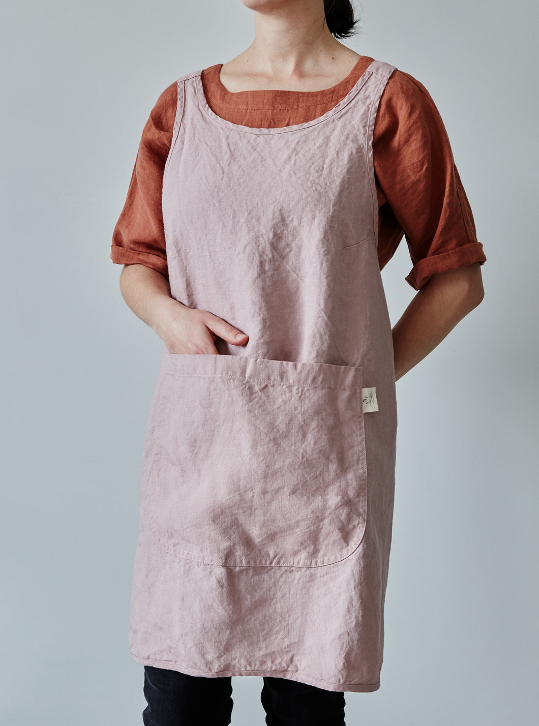 Front of our dusty rose linen apron with a view of the pocket