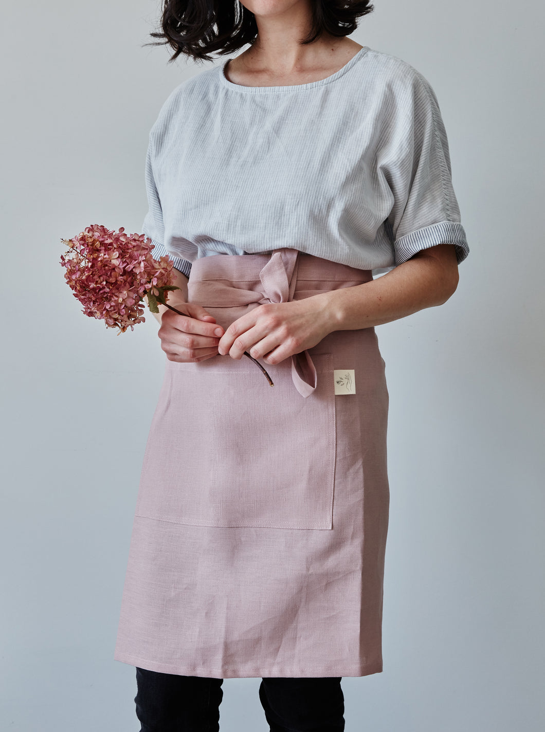 Front of our dusty rose linen half apron with large pocket