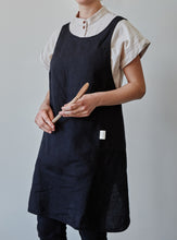 Load image into Gallery viewer, Front of our black linen apron with a view of the pocket