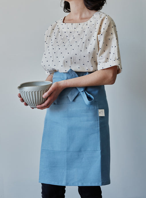 Front of our blue linen half apron with large pocket