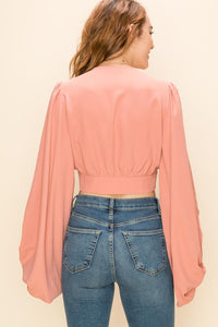 Back view of model wearing a blush/coral pink long sleeved crop top with a delicate button detail.