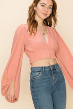 Load image into Gallery viewer, Model is wearing a blush/coral pink long sleeved crop top with a delicate button detail.