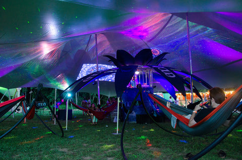 eno hammocks hanging in stands under a large pop-up tent with lights