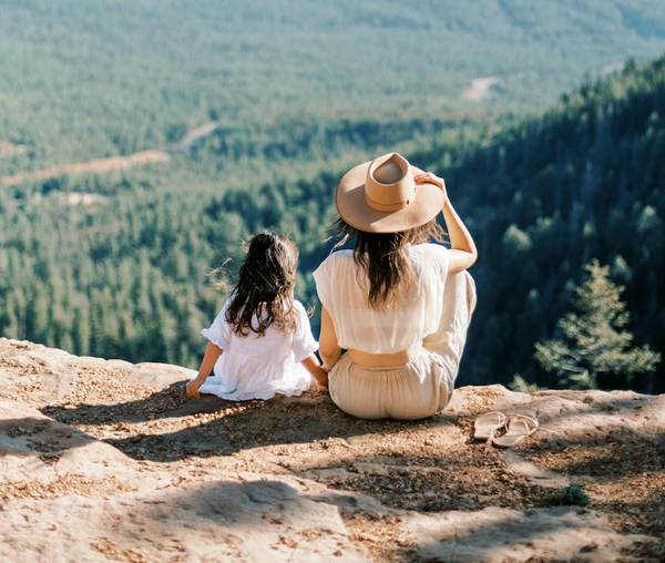 Mom and daughter sitting on ledge of mountain in nature