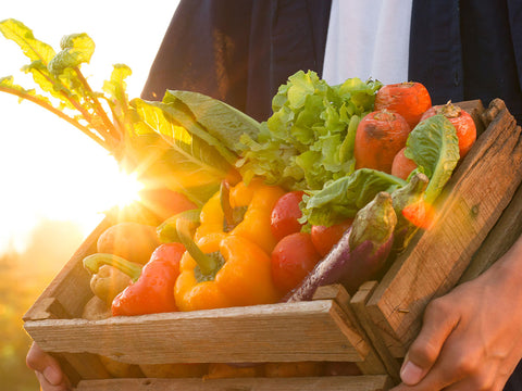 Man holding a crate of vegetables.