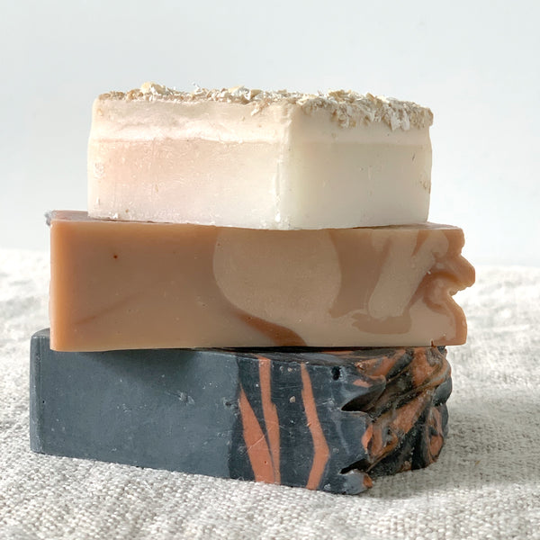 Stack of handmade soaps on a linen towel. Top soap is square and cream colored with oat texture on top. Middle soap is rectangular and rose - white swirled in color. The bottom soap is also rectangular, is a dark gray and clay swirled colored.