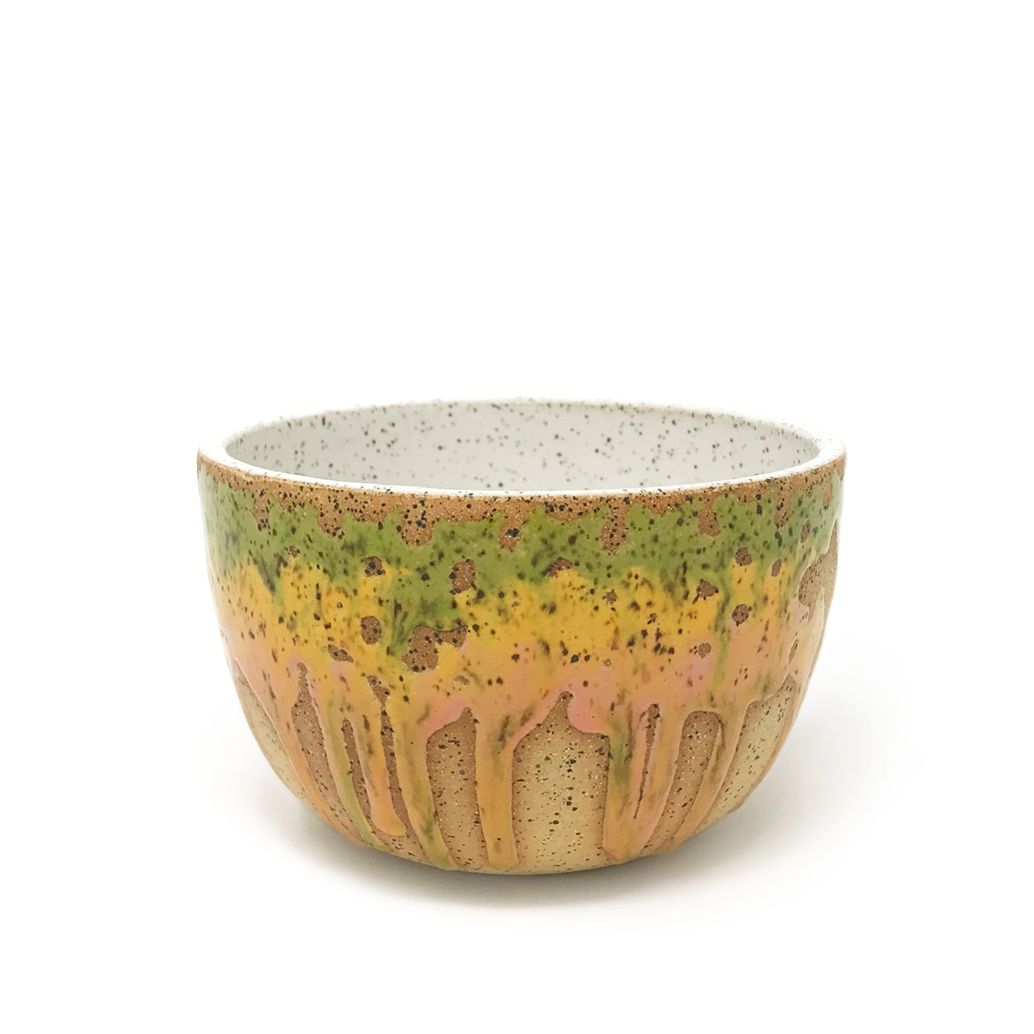Ceramic bowl on a white background. Glaze colors are green, yellow, pinks with a hint of orange.