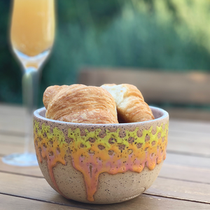 Ceramic bowl with drips of orange and yellow glaze down the sides. Bowl sits on a table filled with croissants and a mimosa flute in the background