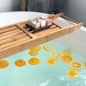 Essential Oil Bath Bombs set on a wood bath tray over a large bathtub filled with citrus slices.
