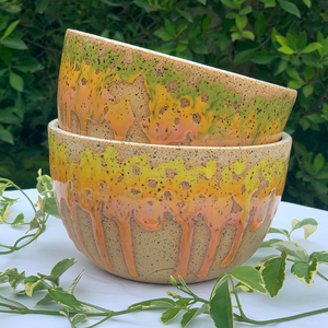 Ceramic Bowls stacked. Top one has green, yellow, and pink glaze dripping down sides. Bottom bowl has yellow and orange glaze dripping down the sides.
