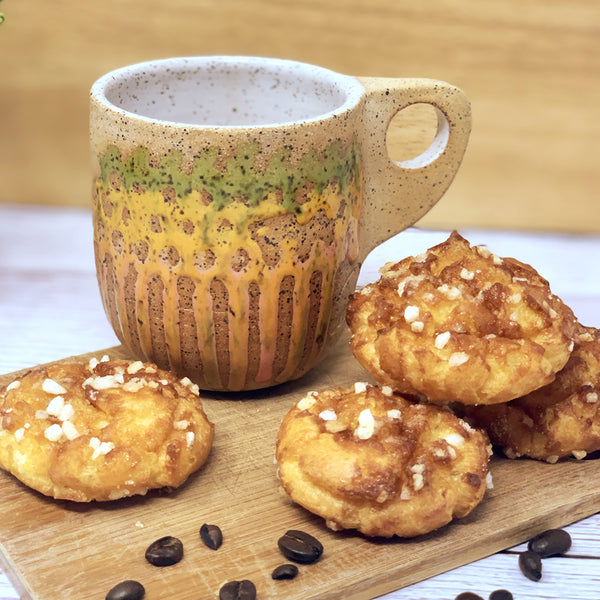 Handmade stoneware mug rests on a wood plank surrounded by puff pastries and coffee beans.
