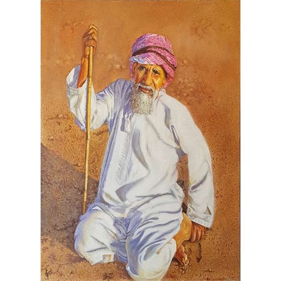 One old Arabian man holding wooden cane stick while kneeling on the sand