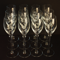 12 Champagne Glasses. Four Different Etched Flower Patterns. Sold in Sets of 4.